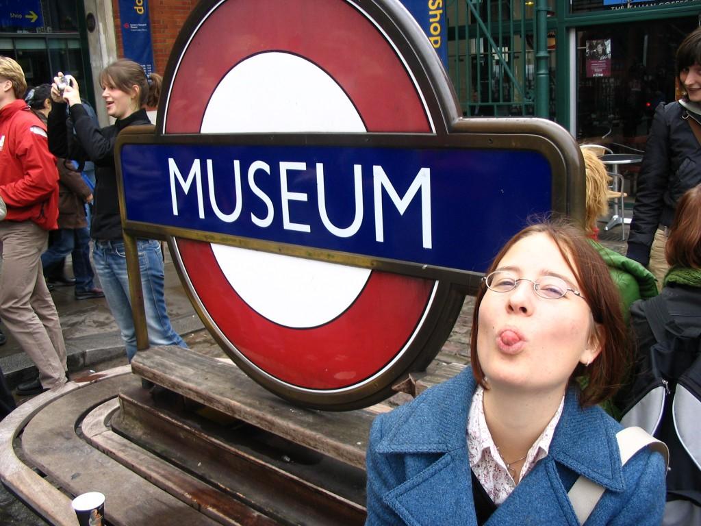 Merel steekt haar tong uit naast een Londen's metro bord met daarop het woord Museum.