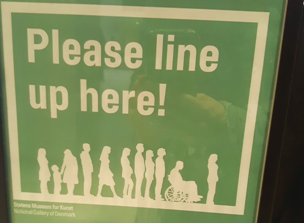 Op het bordje staat de tekst 'please line here!' met daaronder een afbeelding van een rij mensen. In de rij staan mannen en vrouwen, een gezien met kinderen en een rolstoelgebruiker.