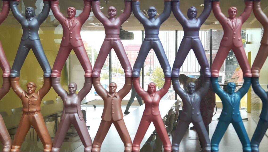 Het kunstwerk is een kamerscherm dat bestaat uit vele kleine gekleurde figuurtjes die als een menselijke piramide op elkaar gestapeld staan.