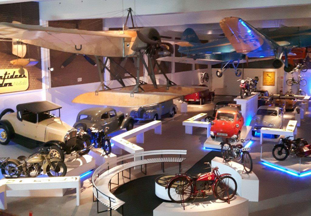 De foto is genomen van de eerste verdieping en kijkt uit over de begane grond waar rijen historische auto's en motoren staan. Erboven hangen historische vliegtuigen.