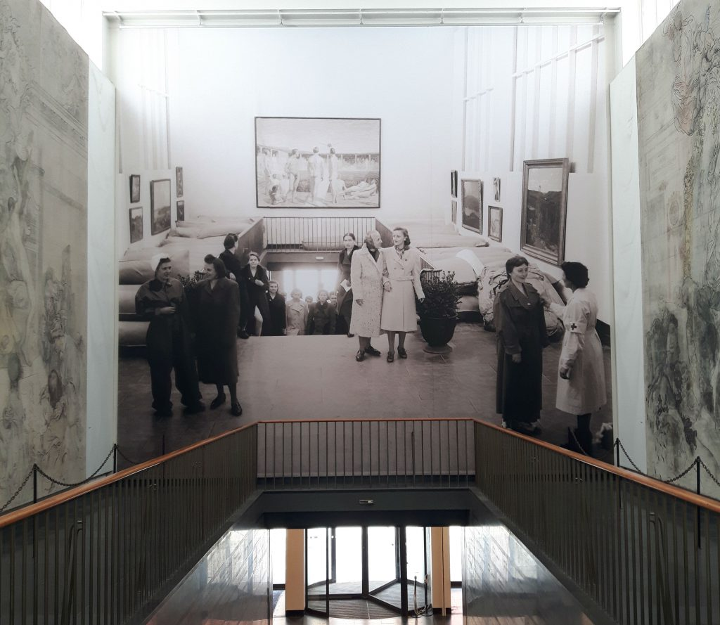De foto toont de hal van het museum met daarin een zwart-wit foto van diezelfde hal. Op de zwart-witfoto is te zien hoe rode kruismedewerkers vluchtelingen opvangen.