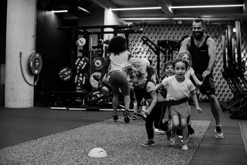 Een groepje van vier lachende kinderen trekken een grote gespierde sportschoodocent voort aan een touw.