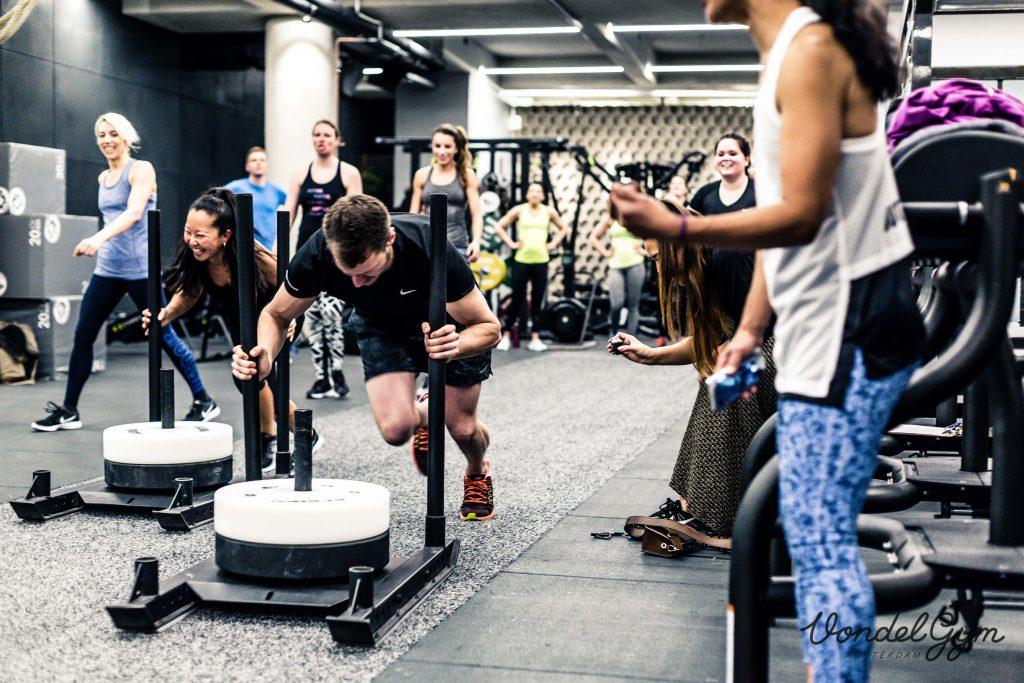 Een foto van twee sporters, een man en een vrouw, die bij wijze van wedstrijd een zwaar object voortduwen. De vrouw lacht. Ze worden aangemoedigd door andere sporters
