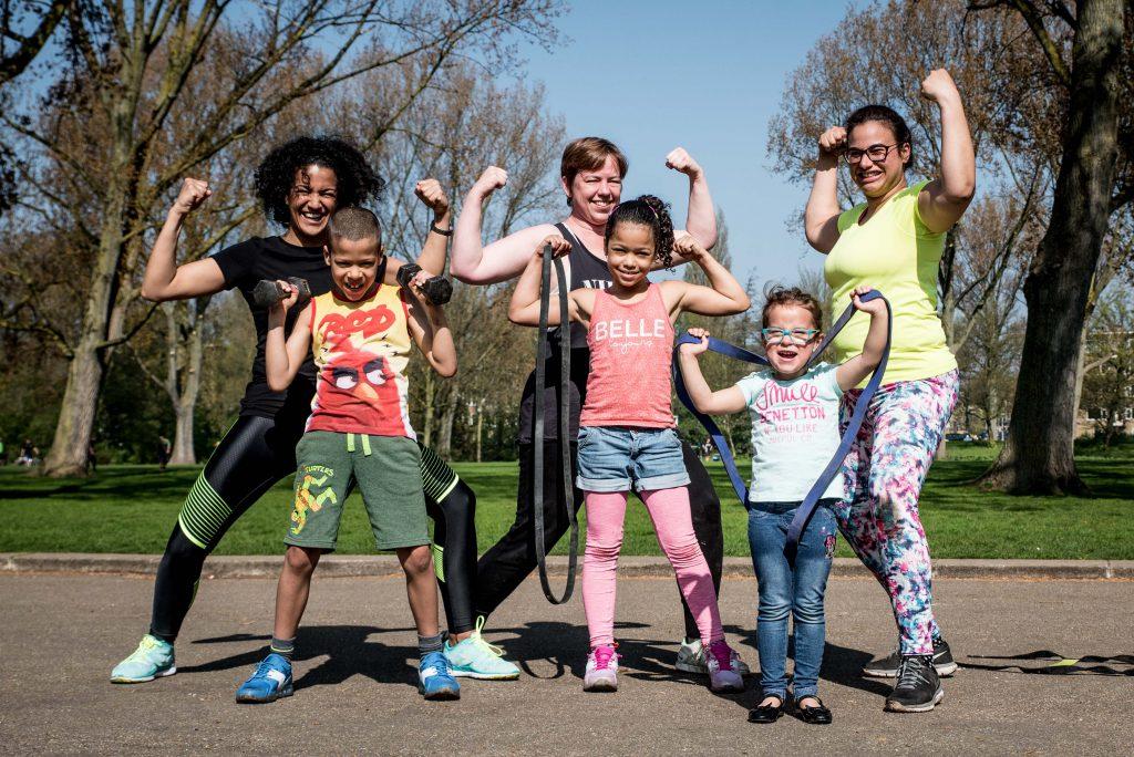 Een docent, twee ouders/verzorgers en drie kinderen tonen trots hun spierballen aan de fotograaf.