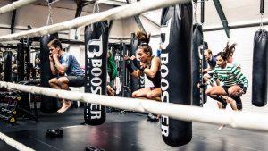 de foto toont zeven sporters die met gebogen benen omhoog springen tussen bokszakken die aan kettingen van het plafond hangen.