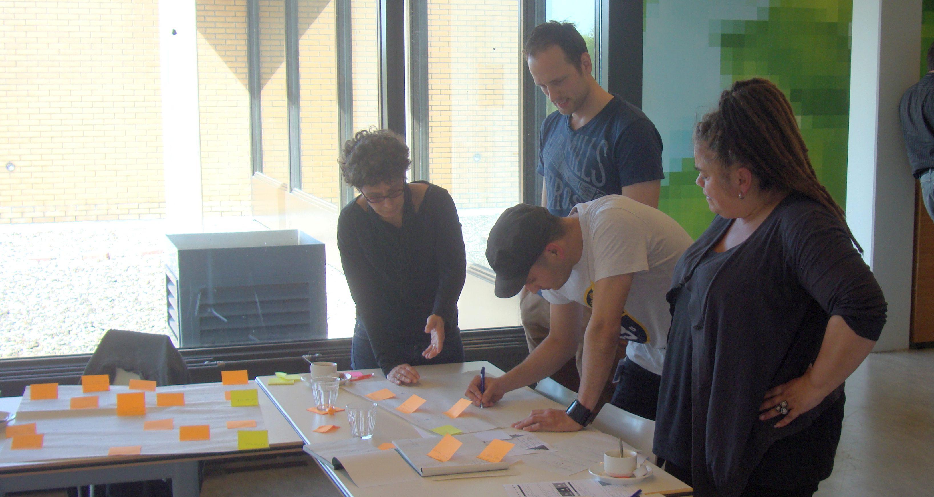 Vier deelnemers van een workshop buigen zich over een opdracht.
