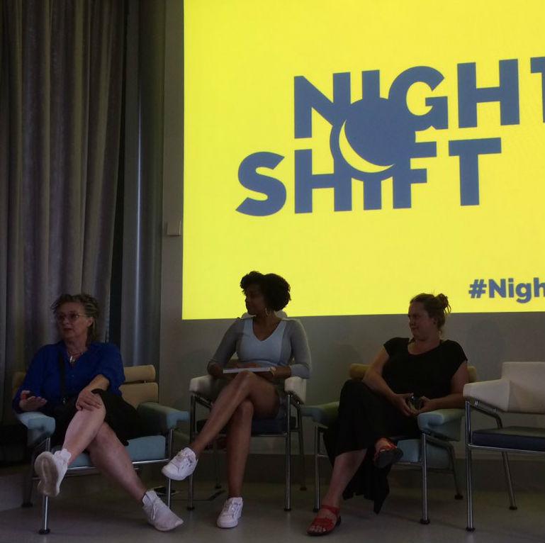 Drie sprekers zitten op stoelen op het podium en zijn in gesprek met de zaal. Achter hen het Night Shift logo