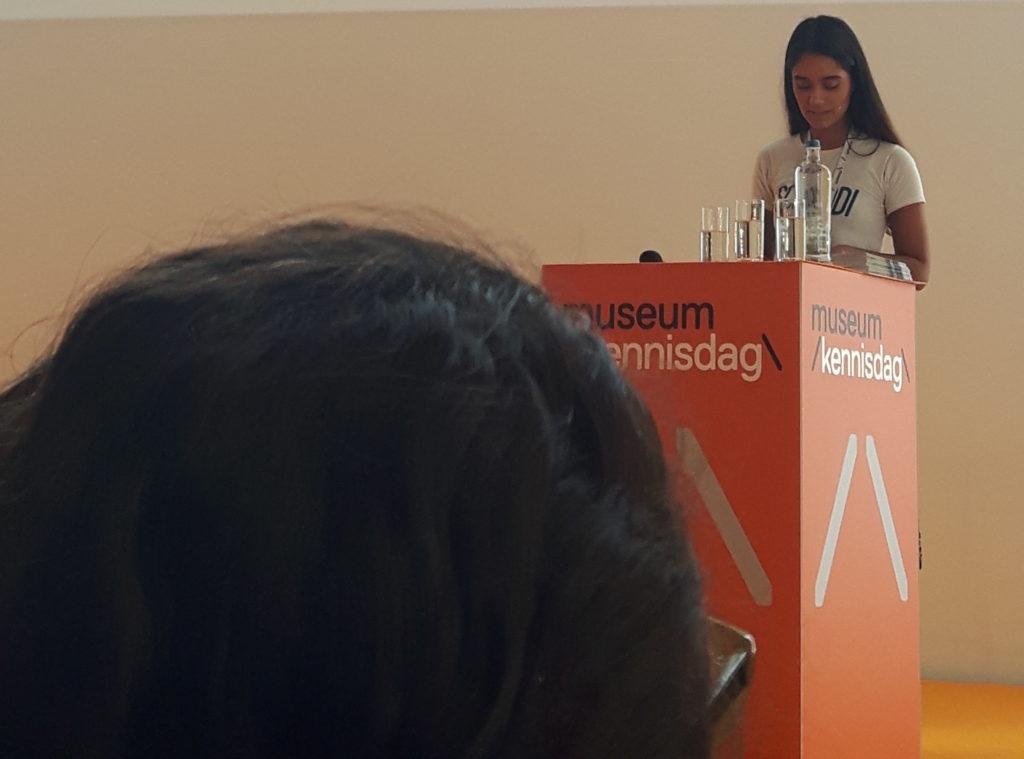 Shaz Hussain geeft haar presentatie, staand achter een sokkkel. Een groot hoofd op de voorgrond blokkeert deels het zicht.