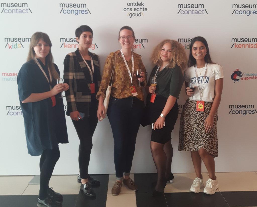 Vijf jonge vrouwen met verschillende culturele achtergronden staan voor een logo-wand van de Museumkennisdag. Sommige van hen hebben een glas wijn in de hand.